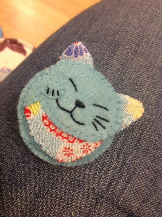 A felt cat brooch. This item is made to order and is available in a variety of colours. The brooch is made from felt with complimentary fabric for