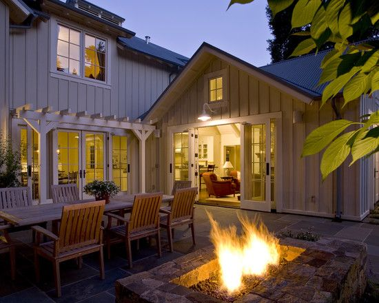 French doors leading to an outdoor family hangout spot with a dining table and fire pit. Love the pergola- adds so much character.