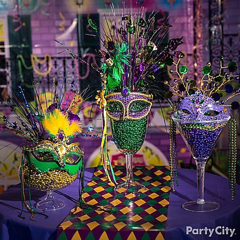 "Centerpiece + grab-and-go Mardi Gras accessories = these easy to make decorations! Everyone will be jazzed over these giant cocktail glasses filled with tons of ""throws"" and adorned with feathered masks!"