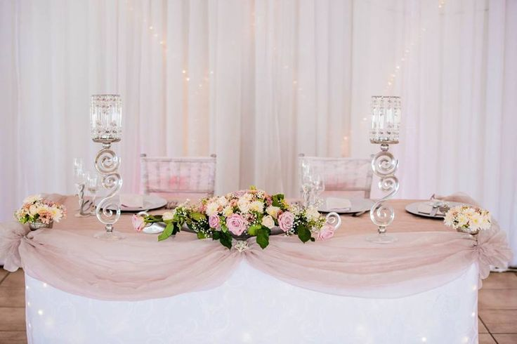 Monte Vista Venue main table setup for a dusty pink wedding. Dusty Pink draping with a white skirt, mixed flowers in rose bowls and rose boats, crystal lampshades with fairy light hearts behind the table