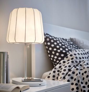 A table lamp with wireless charging, shown on a bedside table next to the bed.
