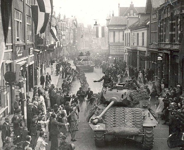 Tanks of the 1st Canadian Armoured Brigade enter Appeldoorn, April 1945. Note the extra tracks welded on to thicken the Sherman's armour.