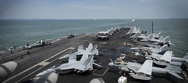 Sailors work on the flight deck of USS Nimitz as it moves through the Strait of Malacca. Look at those jets!