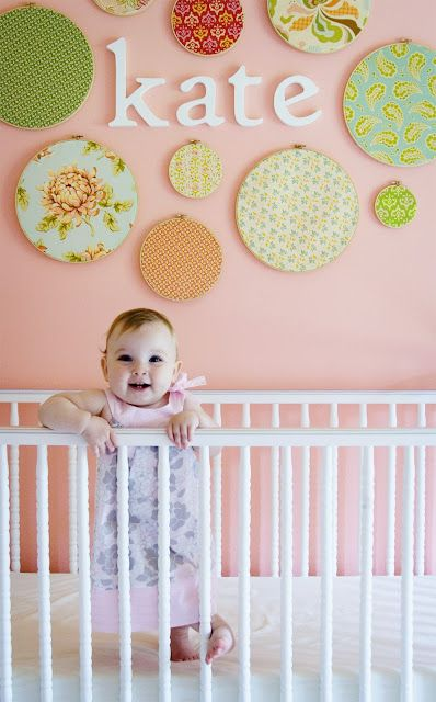 Easy wall decor idea! Simply cut up coordinating fabric and frame in embroidery hoops. Use an extra crib sheet to match your bedding. Also a great spot for monthly milestone pictures!