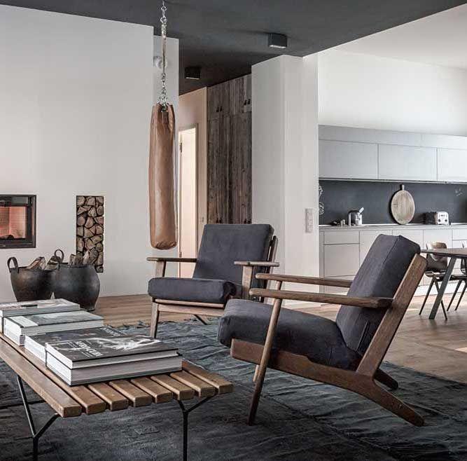Chimenea con leños, mesa de centro y sillones individuales