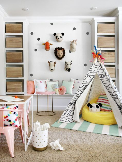 Adorable kid's playroom with pastels, a polka dotted wall, a teepee and wooden boxes for storage