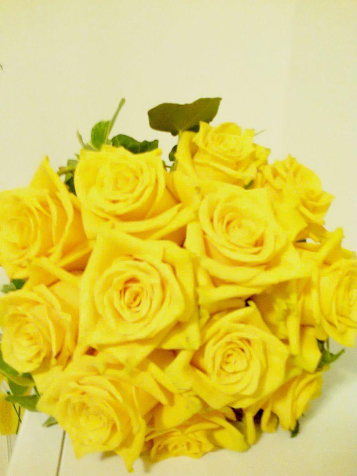 Un bouquet pieno di gioia con le rose gialle e l'edera