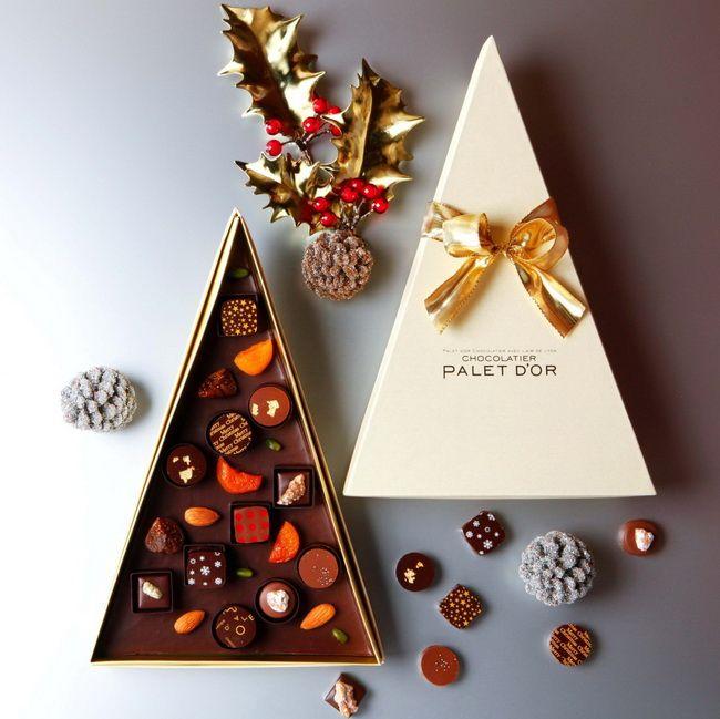 ショコラティエ パレ ド オール(東京・大手町)<br>「クリスマスツリーショコラ」<br>カカオ豆をこのコフレ用にブレンド、焙煎して作った自家製チョコレートのクリスマスツリーに、ボンボンショコラやドライフルーツ、ナッツをちりばめて。ジャンジャンブル(生姜)、エピスなどのボンボンショコラは、全てこのコフレのためだけに手作り。ショコラを一つずつ味わいながらクリスマスを迎えるのも楽しいし、手みやげにも自分へのご褒美にもぴったり。5,000円(税抜)。予約受付中。12/1〜25販売なくなり次第終了。1,000箱限定