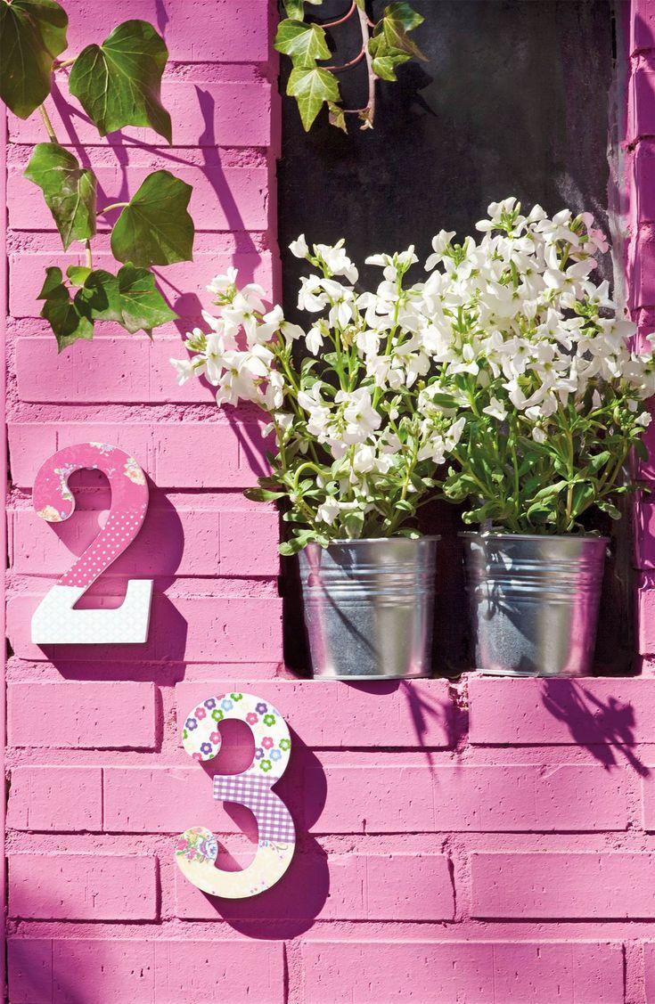 00343809. Pared exterior de ladrillos pintados de color fucsia y con unos números decorativos_00343809