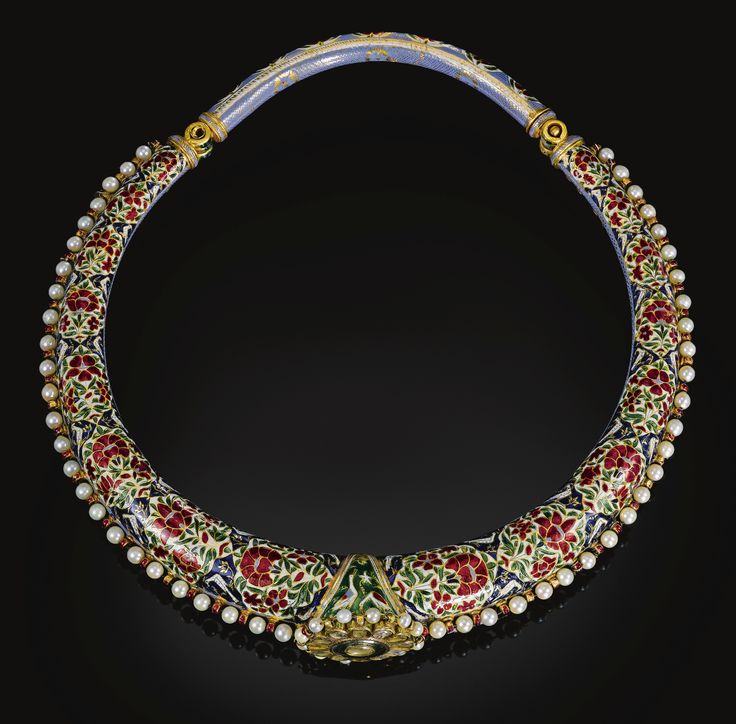 AN ENAMELLED AND GEM-SET TORQUE (HASLI), INDIA, JAIPUR, 19TH CENTURY of rigid ovoid from, with an applied diamond-set rosette to the centre and bridge and pin clasp, the upper side decorated with diamond flowerheads and leaves reserved against a blue enamelled ground, the reverse decorated in red, green, white and blue enamels with cartouches of alternating flowerheads flanked by birds, the edges bordered with pale blue enamelling and pearls 18.2cm. max. diam.