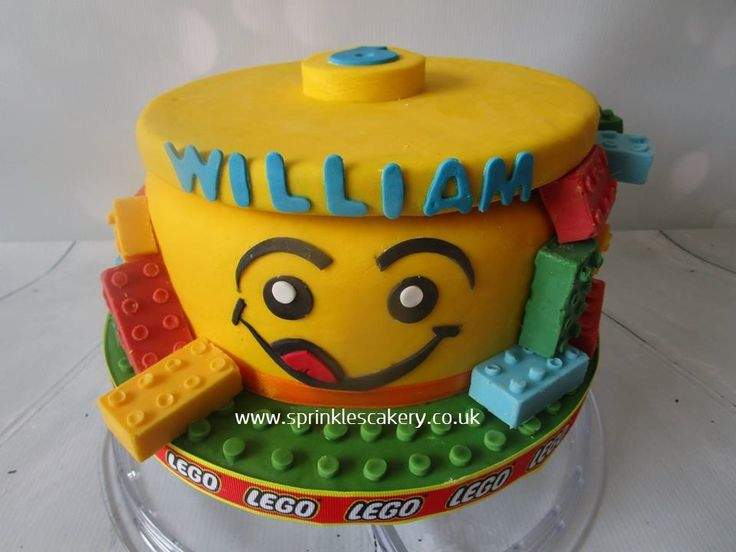 A lego head dummy cake decorated in fondant and finished with hand crafted candy lego bricks.