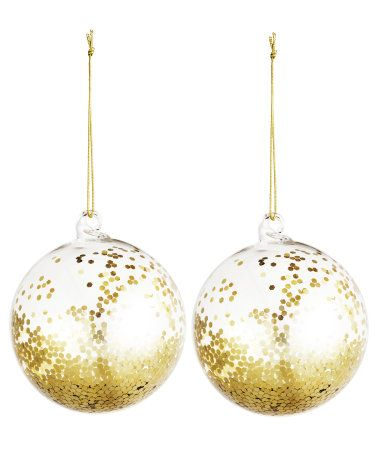 Glass Christmas ornaments filled with glittery confetti. Glass hanger loop with hanger cord. Diameter 3 1/4 in.