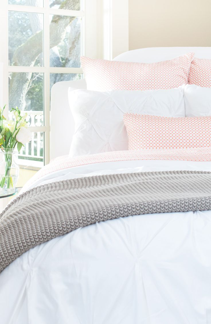 Beautiful white bedding layered with neutrals and a splash of color. Shop the look at  craneandcanopy.com.