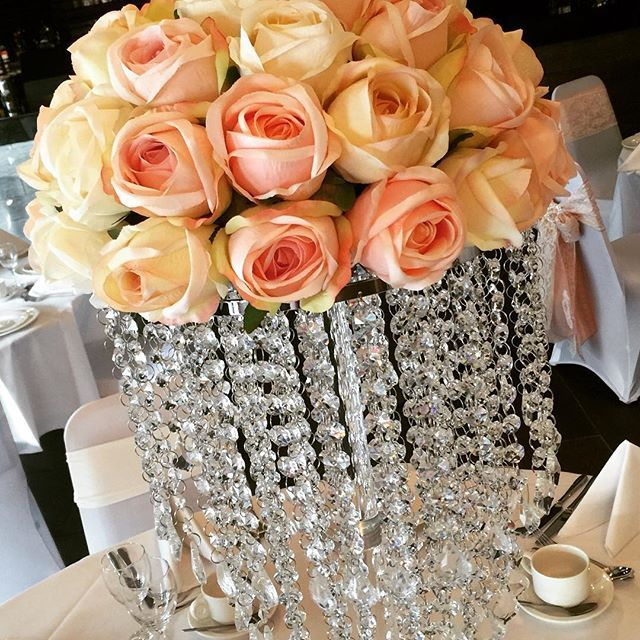 Beautiful crystal chandelier stand and blush roses, the perfect centrepiece. #understatedbling #weddingdecor #weddingideas #sensationaleventsuk #blush