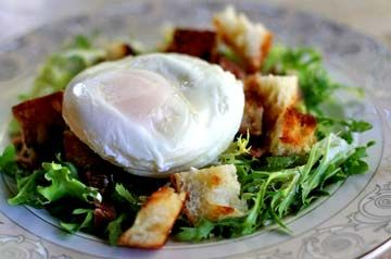 Traditional French salad Lyonnaise with frisee lettuce, bacon, croutons, a poached egg, and a Dijon vinaigrette.