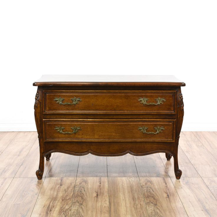 This short dresser is featured in a solid wood with a glossy oak finish. This French Provincial style chest of drawers has 2 spacious drawers, curved trim, carved floral accents, and ornate brass hardware. Charming piece that's perfect for storing clothing! #americantraditional #dressers #shortdresser #sandiegovintage #vintagefurniture