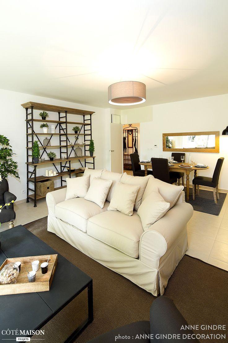 Salon aux murs blancs. Canapé dans la même teinte, confortable avec tous ces oreillers ! Table basse noire. Tapis marron.