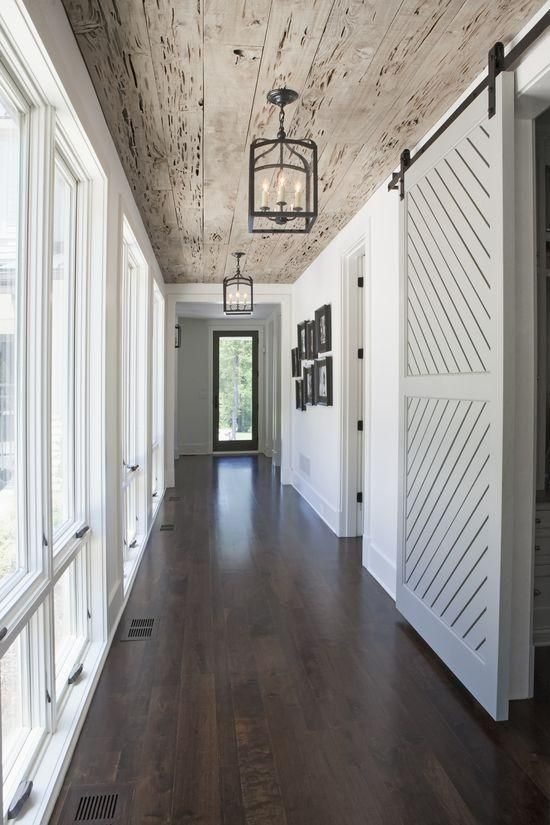Check out this rustic hallway!  We love the dark wood floors with the reclaimed wood ceiling.  The white sliding barn door adds a dramatic effect.  The cage pendant lights down this hallway gives it a dramatic and gorgeous look!  Add some rustic elegance to your home!