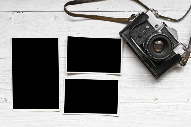vintage retro camera on wood table background with blank photos