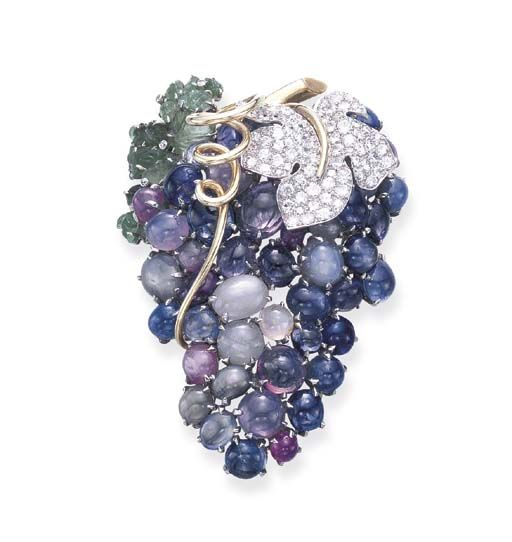 A SAPPHIRE, DIAMOND AND EMERALD 'BUNCH OF GRAPES' CLIP BROOCH, BY SEAMAN SCHEPPS