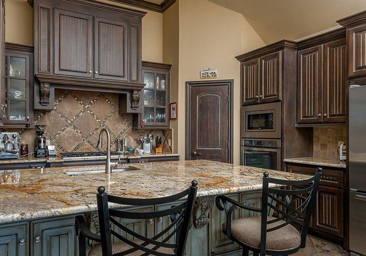 Rich dark wood cabinet kitchen with distressed wood island.