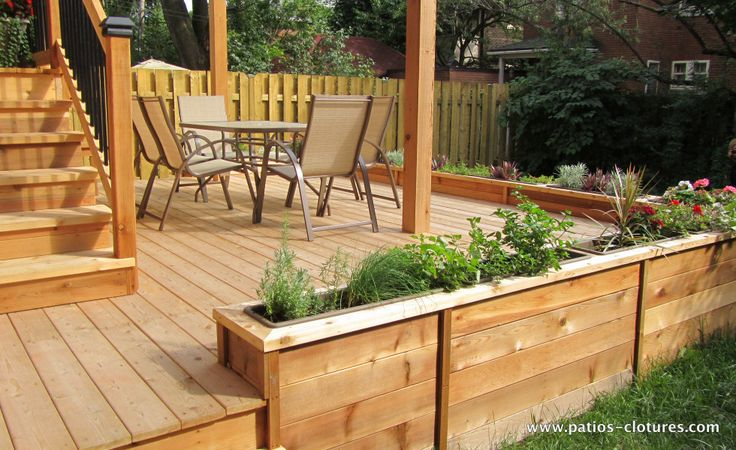 Flower boxes around the low terace of a two story deck for Garden decking near me