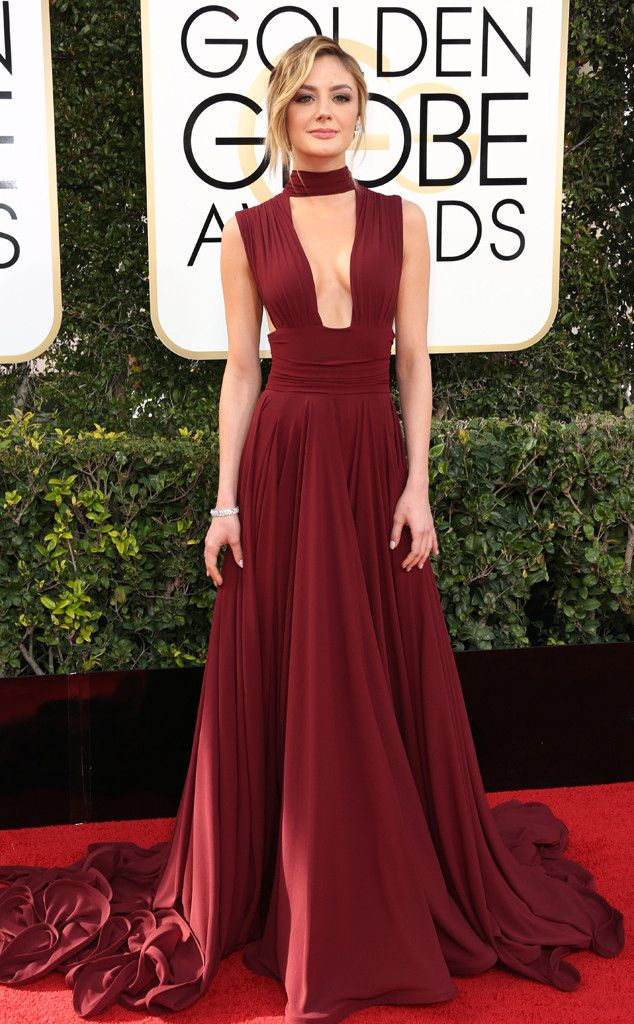 Christine Evangelista in a deep dark red gown with open neckline that extends a single thick strap around her neck. Hair in a loose wavy bun.