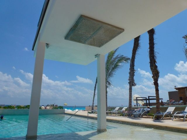 Rain shower at the Barefoot Pool at Secrets The Vine hotel in Cancun Mexico