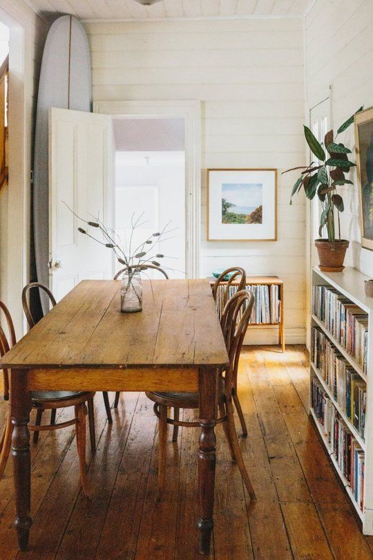 Quaint and cosy old cottage dining room with wooden table, bentwood chairs, bookcase and indoor plants. Photo: Sophie Timothy