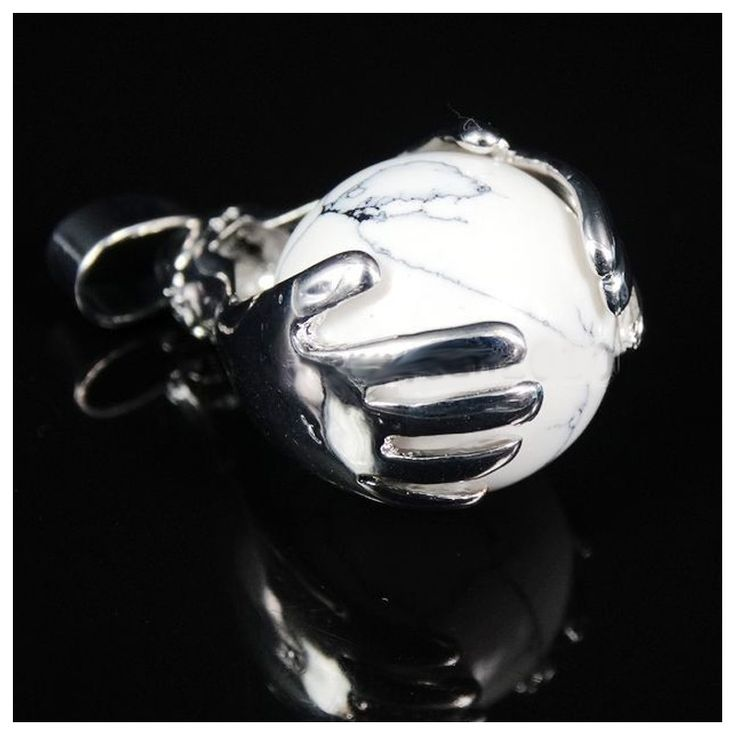 """Healing Hands Howliet """"VREDE"""" Verzilverde metalen hanger met een howliet bol ingeklemd tussen twee helende handen. Een symbool van bescherming en spiritualiteit. Howliet is de steen van vrede, acceptatie en eigenheid. De steen helpt je om je eigen koers te varen, en om tevreden te zijn met wie je bent. Fysiek heeft de steen een positieve werking op slaapproblemen."""