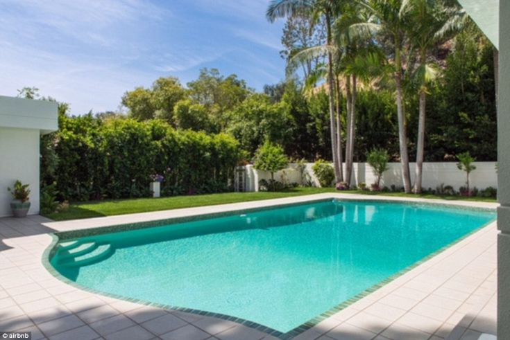 The best part: The contemporary crash pad features a lovely yard and lengthy modern pool...