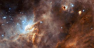 The NASA/ESA Hubble Space Telescope captures the iridescent tapestry of star birth in a neighbouring galaxy in this panoramic view of glowing gas, dark dust clouds, and young, hot stars. The star-forming region, catalogued as N11B lies in the Large Magellanic Cloud (LMC), located only 160,000 light-years from Earth