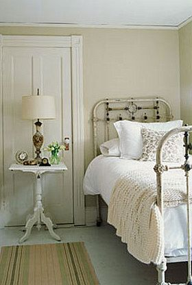 Farm house guest bedroom: wrought iron beds, antique white, pedestal table.