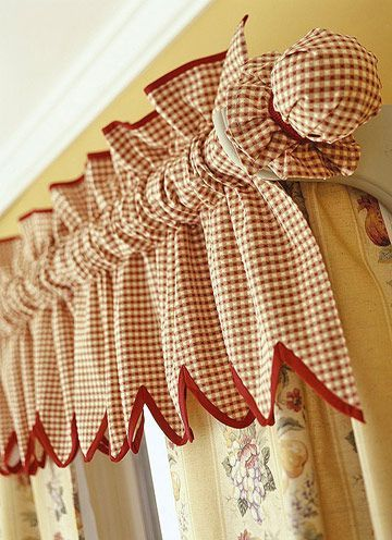 Incorporate the curtain rod into the window topper by covering it with matching fabric. Combine a creative topper with plain panels to draw the eye upward toward the topper. This gives an illusion of height to the kitchen. Here, ball finials are covered by hemmed circles of matching gingham fabric. Gimp ties the covers in place.