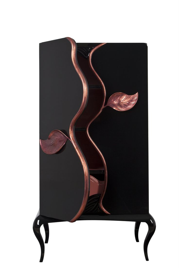 Furniture inspired by nature, with an organic form and doors whose finishes follow the movement of the branches, ending up in two leaves – hand-sculpted handles made by Greek walnut and finished with brass sheet. The furniture has a black glossy lacquer finish and its base is made by 'IROCO' wood.