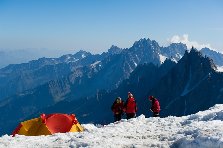 A group of climbers prepares for a long acclimatization climb from the summit of Aiguille Gouter overlooking Chamonix Valley and famous Aiguille du Midi. Photograph taken during summer traverse of Mont Blanc, France.