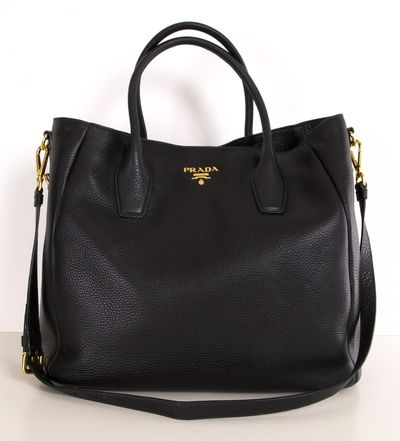 """A stunning black leather Prada tote, new and never used with the dust bag and authenticity cards. emovable, buckled shoulder strap with 17"""" drop. Inside, logo lining; one zip and one open pocket with snap button closure. 14""""H x 16""""W x 5 1/4""""D; weighs approx. 12oz. Made in Italy."""