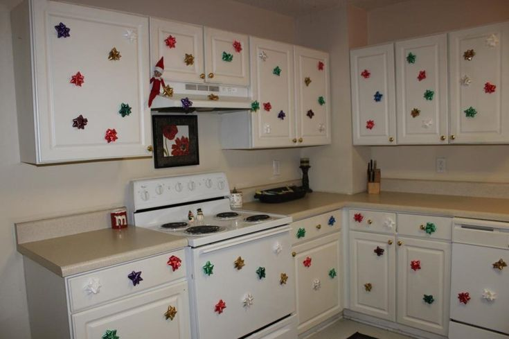 Elf on shelf decorates kitchen with sticky bows.