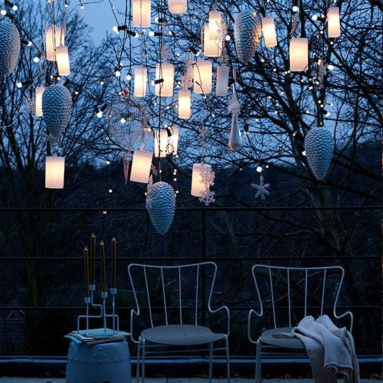 Create a magical winter seating area by hanging a cluster of lantern lights and white Christmas decorations over a patio.