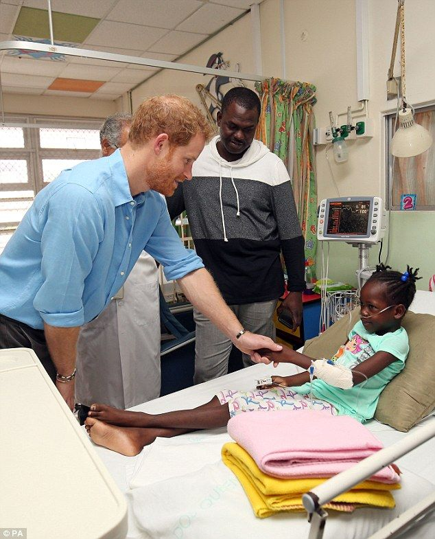 Making friends: Harry tries to get a smile out of the little girl as he makes his way arou...