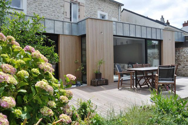 Contemporary extension on old frame, consistency is ensured by the subtle marriage of materials (stones / wood / zinc).  Originally, the house was covered with a cement coating.  The discovery of the beautiful stones gave a whole new dimension to the project.