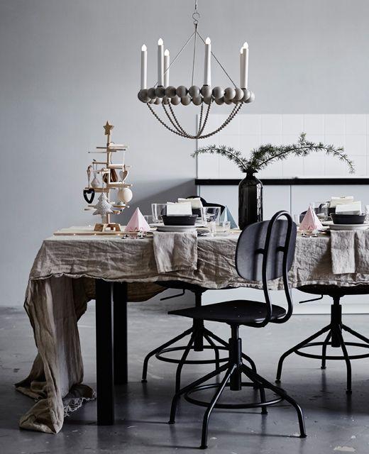 Jedálenský stôl ozdobený origami v pastelových farbách, vetvičkami vo váze a drevenou doskou uprostred stola.