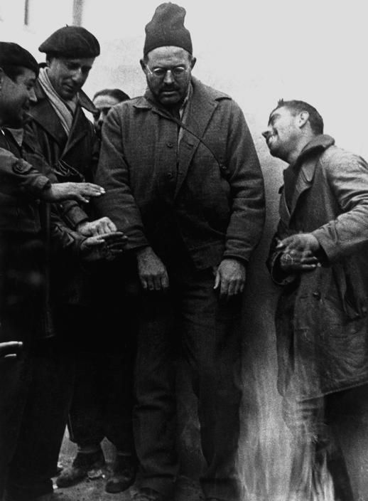 Robert Capa. Valencia, Spain. Ernest Hemingway visiting the front lines. December 1937