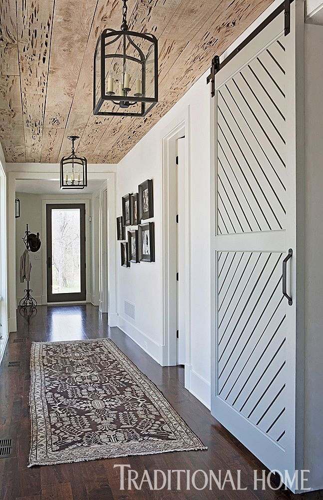 A sliding barn door and pecky cypress ceiling turn an ordinary side hallway into a stunning entrance.