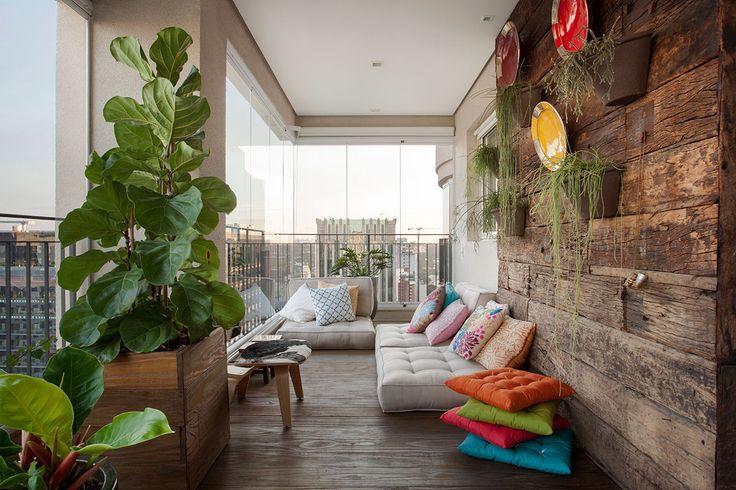 Decoração de apartamento com ambientes integrados e varanda. Varanda com futon branco, almofadas estampadas, revestimento de madeiras e plantas na decoração.