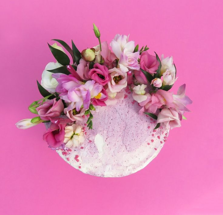 Pink Iced Cake Decorated With Fresh Flowers By The