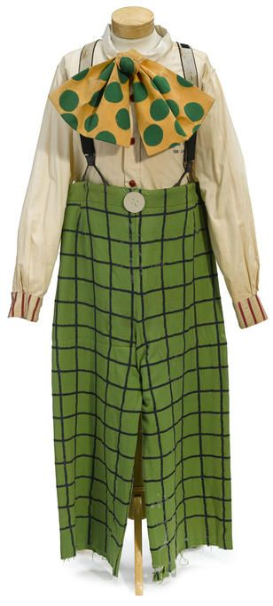 A Jimmy Stewart clown costume from The Greatest Show on Earth, 1952. A beige cotton shirt with red buttons and red striped cuffs. Together with a high-waisted, wide leg pair of kelly green and navy checked wool pants with black braces. The yellow cotton bow tie has green felt polka dots and an elastic tie to secure it around the neck