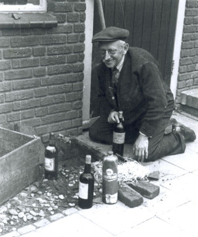 A citizen of the town Zwolle,Netherlands is digging up his liquor stash after the Liberation. April 14th, 1945.