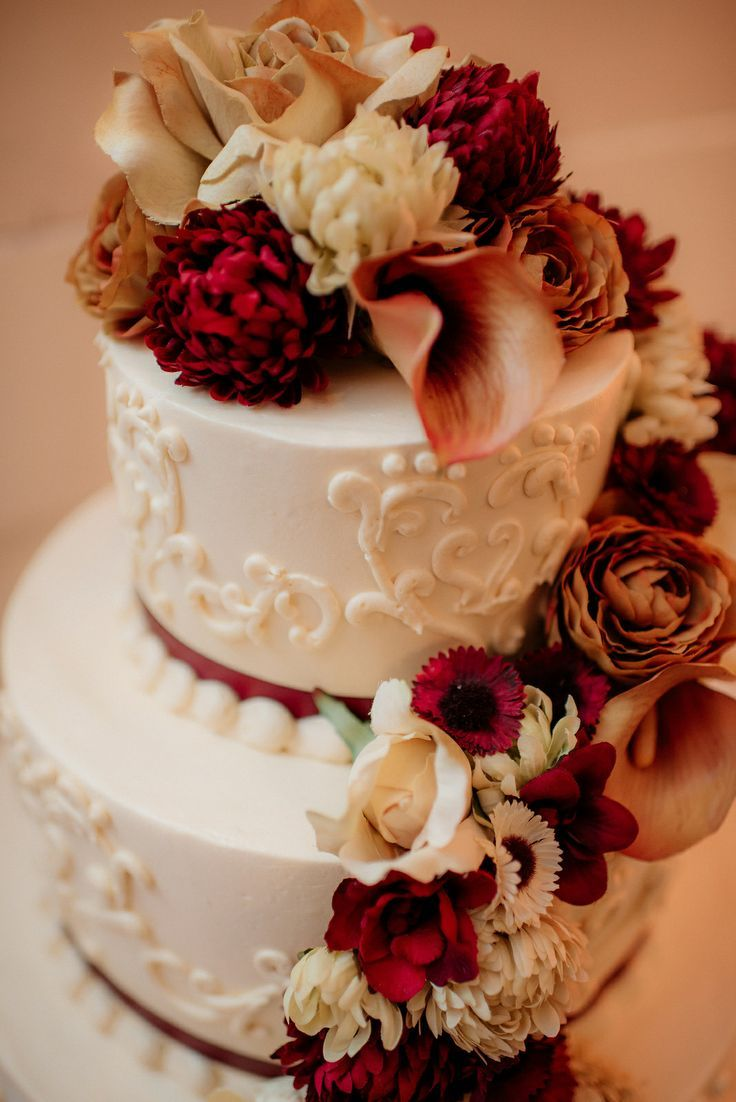 Gorgeous fall-themed wedding cake. Pale pink, brown ribbon, and colored flowers....Lisa