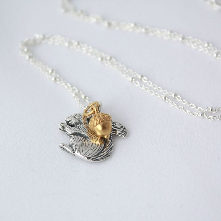 Sylvie Necklace. Gold and silver necklace of squirrel and acorn charms.